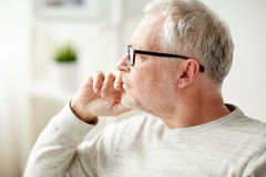 Close up of senior man in glasses thinking Stock Photo