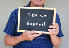 Close up of senior man holding blackboard with the phrase ask an expert written on to Royalty Free Stock Photos