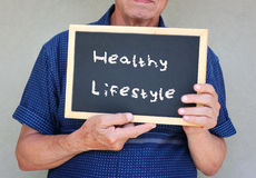 Close up of senior man holding a blackboard with the phrase good health equals good life Stock Images