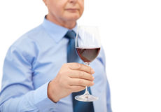 Close up of senior man holding glass with red wine. Profession, winery, drinks, holidays and people concept - close up of senior man holding glass with red wine Stock Photography
