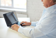 Close up of senior man with laptop typing Stock Photo