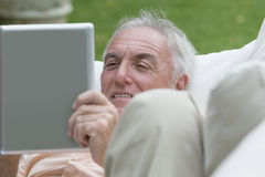 Close up of senior man laying on outdoor sofa and using digital tablet stock photography