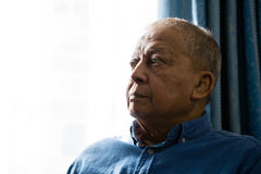 Close up of senior man looking away while sitting by window Royalty Free Stock Photos