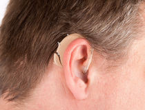 Close-up of a senior man`s ear with a behind-the-ear-hearing dev Royalty Free Stock Photos