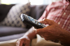 Close Up Of Senior Man Sitting On Sofa Holding TV Remote stock photography