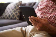 Close Up Of Senior Man Sitting On Sofa Using Digital Tablet Royalty Free Stock Photo