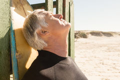 Close up of senior man standing by surfboard Royalty Free Stock Image