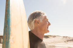 Close up of senior man with surfboard standing against clear sky Stock Photo