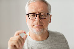 Close up of senior man taking medicine pill. Age, medicine, health care and people concept - close up of senior man taking medicine pill at home Royalty Free Stock Photo