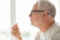 Close up of senior man taking medicine pill. Age, medicine, health care and people concept - close up of senior man taking medicine pill at home Stock Image