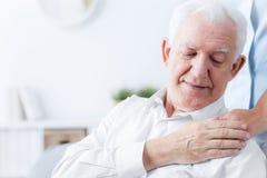 Close-up of senior man touching hand of friendly caregiver. Close-up of senior men touching hand of friendly caregiver concept photo stock image