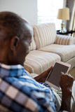 Close up of senior man using tablet. While sitting on sofa at home Royalty Free Stock Photo