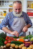 Close-up of a senior man wearing an apron and chopping some vege Royalty Free Stock Photo