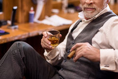 Close up of senior man with whiskey glass and cigar Stock Photo