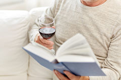 Close up of senior man with wine reading book Stock Photography