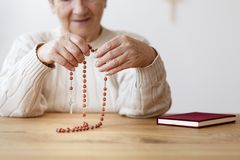 Senior person praying with rosary royalty free stock photo