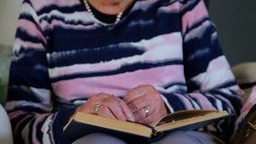 Senior woman reading a book in living room stock video
