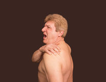 Close-up of senior shirtless man with shoulder pain over black background. Close-up of senior shirtless man with shoulder pain over white background royalty free stock image