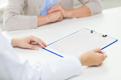 Close up of senior woman and doctor with clipboard Stock Image
