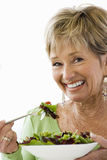 Close-up of senior woman eating bowl of salad, cut out Royalty Free Stock Image
