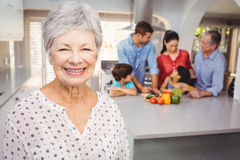 Close-up of senior woman with family preparing food in background Royalty Free Stock Photos