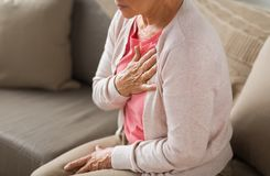 Close up of senior woman having heartache at home. Old age, health problem and people concept - close up of senior woman suffering from heartache at home Royalty Free Stock Photography