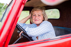 Close up of senior woman inside vintage pickup truck Stock Photo
