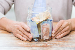 Close up of senior woman with money in glass jar Stock Image