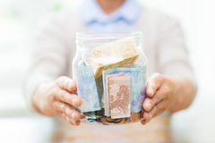 Close up of senior woman with money in glass jar Stock Photos