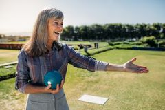 Cheerful senior woman standing in a lawn holding a boule stock images