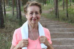 Close Up Of Senior Woman Running In Park Listening To Music Holding a Towel Stock Image