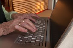 Close up of senior woman`s hands working on computer keyboard. Close up of old hands typing on modern laptop keyboard royalty free stock image