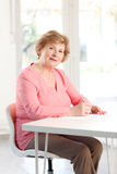 Close-up of a senior woman sitting at desk Stock Photography