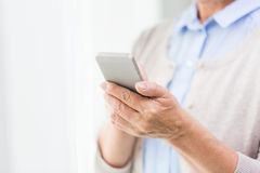 Close up of senior woman with smartphone texting Royalty Free Stock Images