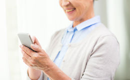 Close up of senior woman with smartphone texting Stock Images
