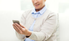 Close up of senior woman with smartphone texting Stock Photo