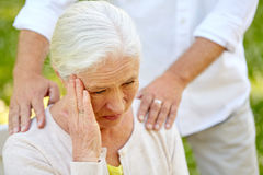 Close up of senior woman suffering from headache. Health, stress, old age and people concept - close up of senior woman suffering from headache outdoors Stock Photo