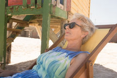 Close up of senior woman with sunglasses resting on chair. At beach Royalty Free Stock Image