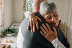 Close up of a senior woman embracing her husband with closed eyes standing in kitchen. Elderly couple hugging each other royalty free stock photos