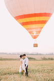The close-up sensitive portrait of the newlyweds couple hugging at the front of the airballoon. The bride is holding the Royalty Free Stock Image