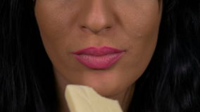 Close-up of sensual female lips tasting white chocolate. Closeup of sensual female lips tasting white chocolate stock footage