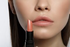 Voluptuous young woman doing makeup. Close up of sensual girl holding pink lipstick near her mouth. Lip beauty concept Royalty Free Stock Photography