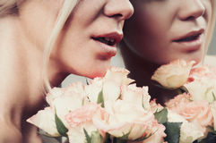 Close up sensual smile woman lips in pastel color with bouquet o Stock Image