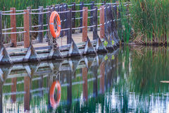 Close up of serene floating boardwalk with orange life preserver Stock Photo