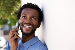 Close up serious black man talking on mobile phone outside. Close up portrait of serious black man talking on mobile phone outside royalty free stock photos