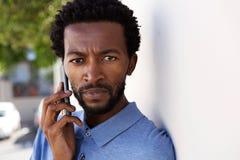 Close up serious black man talking on mobile phone outside. Close up portrait of serious black man talking on mobile phone outside stock photos