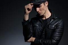 Close up a serious looking man adjusting his cap. And confidently staring to the camera while wearing a black leather jacket and standing on white studio stock photos