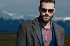 Close up of serious looking man staring to the camera. While wearing a gray coat, blue suit, sunglasses, and checkered shirt while standing on outdoor stock image