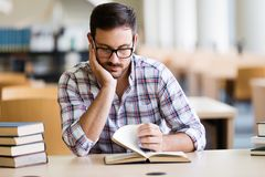 Serious male student reading book in the college library royalty free stock image