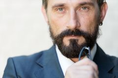 Close up of serious man looking at you and thinking royalty free stock image
